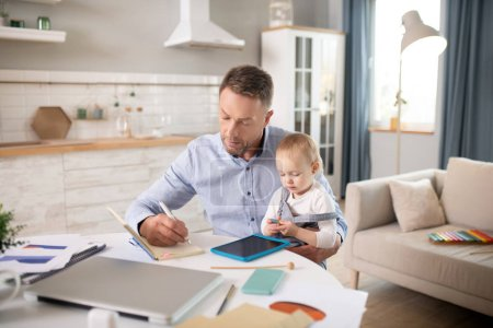 Photo for Concentrated. Bearded man in a blue shirt holding his kid and looking serious - Royalty Free Image
