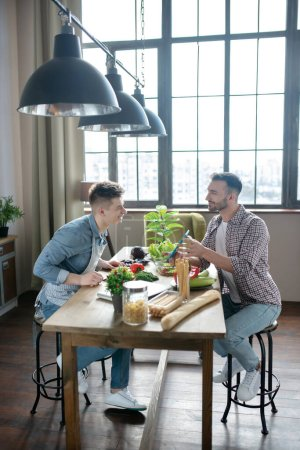 Photo pour Day off. Two men sitting opposite each other near a table with vegetarian products, one shows the other a tablet, joyful. - image libre de droit