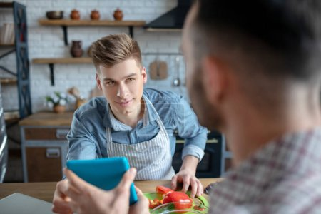 Photo pour Communication. Dark-haired man sitting with his back showing a tablet to a blond-haired guy preparing a salad, in a good mood. - image libre de droit