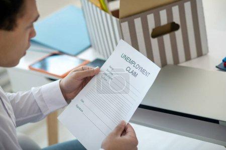 Photo pour Au travail. Jeune brune brune assise à son bureau, tenant une demande d'assurance-chômage - image libre de droit