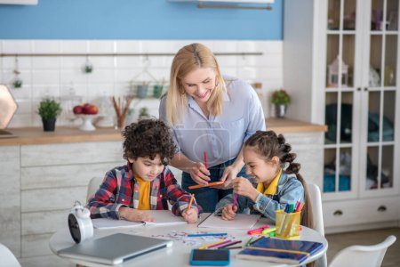 Photo for At home. Curly boy and dark-haired girl sitting at table, doing their assignments, blonde female standing above them, helping - Royalty Free Image