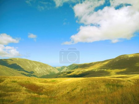 mountain with clouds in blue sky