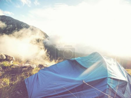 mountain with tent in sunny morning