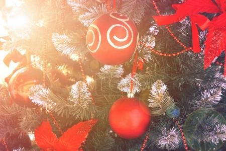Christmas background with holiday ball on fir-tree with snow and bokeh lights