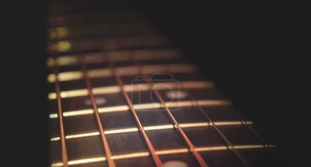 Closeup of guitar neck in diagonal position with strings in copper colour on black background