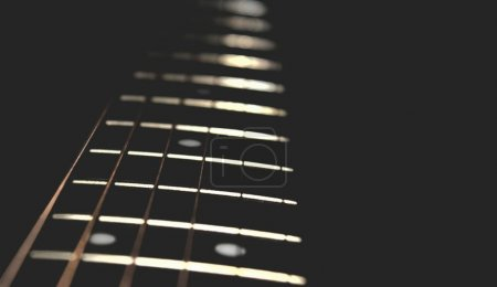 Closeup of guitar neck in vertical position with strings in silver colour on black background