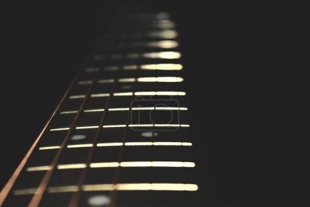 Photo for Closeup of guitar neck in vertical position with strings in silver colour on black background - Royalty Free Image