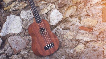 close-up photo of Ukulele wooden guitar on stoned background