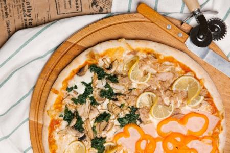 Gourmet pizza with ham, tuna, bell pepper pieces, mushrooms, spinach and lemon slices served on wooden tray with wine