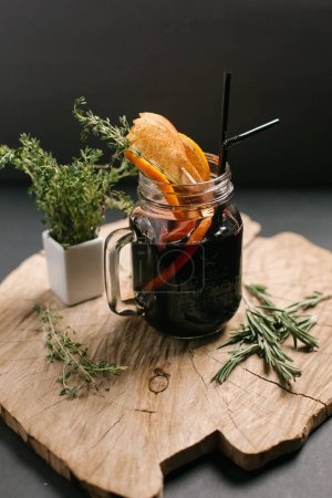 Hot mulled wine served with orange slices and rosemary in glass mug