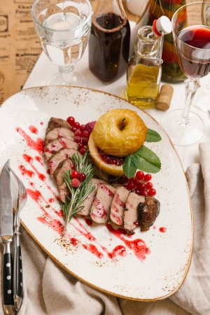 Holiday dish with baked duck breast, apple, cranberries and rosemary