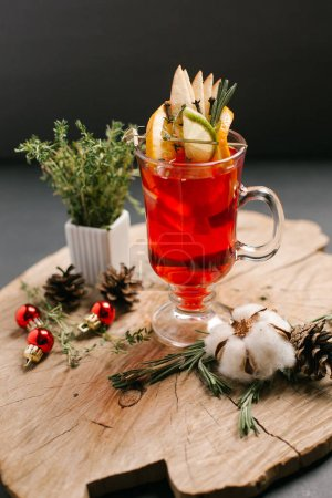 Festive sweet beverage including cranberries, lemon, lime slices and honey decorated with christmas balls, pine cones and rosemary branches served on sawed wood