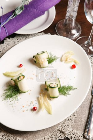 Stuffed zucchini with shrimps served with pepper pieces and dill on white plate