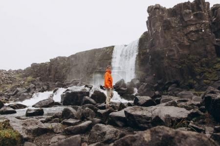Young man walking near waterfall in gloomy day