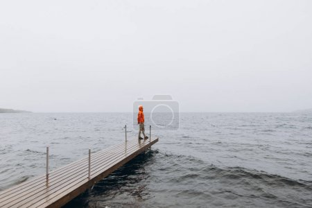 Photo for Young man standing on pier in rainy day - Royalty Free Image