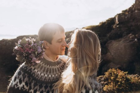 Young lovely couple dressed in knitted jumpers embracing and  basking in sun