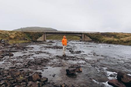 View of man walking near river with bridge in cold rainy day