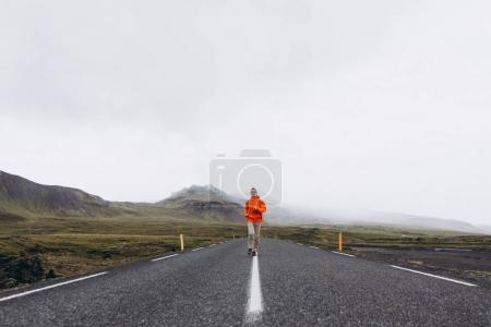 Front view of man running by the road in gloomy day