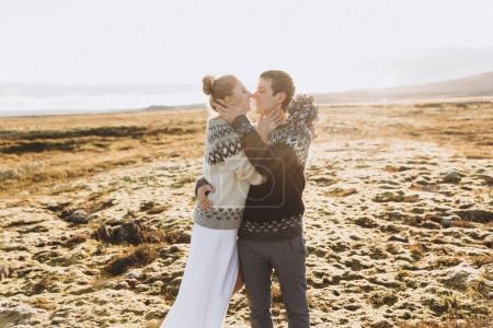 Young couple kissing in warm knitted sweaters and young woman holding pretty flower bouquet