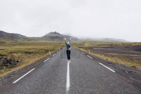 Vue de face de la jeune femme sur la route des sauts de jour de pluie froide sur fond de montagnes