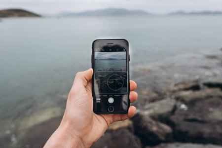 Photo for View of man standing near stones and taking photo of nature with smartphone - Royalty Free Image