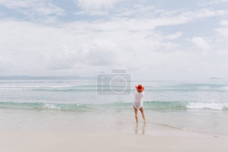 view of young female in red hat on sandy seacoast with rainy clouds in sky