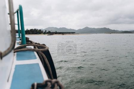 View from boat on island on cloudy grey sky background