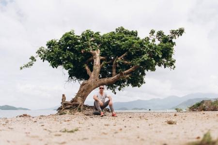 View of man sitting on the beach near tree with monkey
