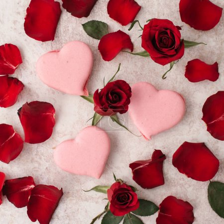 Valentines day background with festive pink cookies and red petals on background