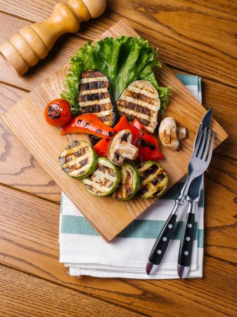Top view of grilled eggplants, tomato, peppers, mushrooms and zucchini served on wooden cutting board with lettuce and cutlery