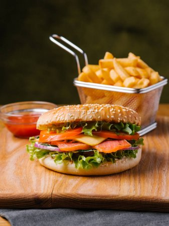 Tasty meal including salmon cheeseburger, french fries in basket and sweet ketchup serving on wooden cutting board and grey napkin