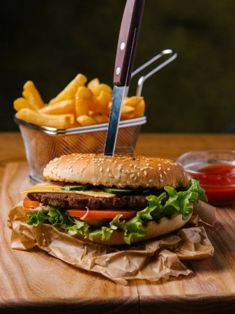 Cheeseburger with knife inside, french fries in basket and sweet ketchup served on wooden chopping board