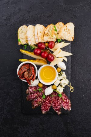 Photo for Cheese, salamis and breads sliced with honey and sun dried tomatoes on black plate - Royalty Free Image