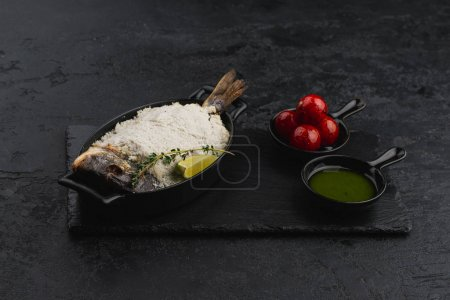 Photo for Baked trout in salt with sauce pesto and tomatoes on black background - Royalty Free Image
