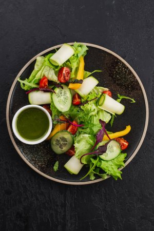 Photo for Colored fresh vegetables salad with pesto sauce on black background - Royalty Free Image
