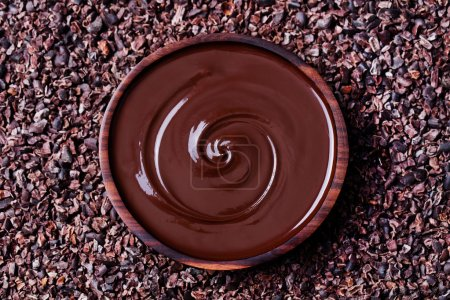 Bowl of melted chocolate on a crushed raw cocoa be...
