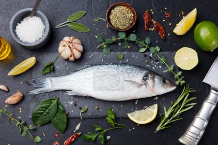 Photo for Raw fish, sea bass on slate black board. Ingredients for cooking, grill, roasting. Top view Copy space - Royalty Free Image
