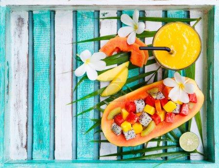 Photo pour Salade de fruits tropicaux dans la moitié de la papaye avec jus de mangue, smoothie. Vue de dessus. Espace de copie - image libre de droit