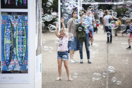 LONDON, ENGLAND - AUGUST 22, 2017 the girl playing with soap bubbles at south bank