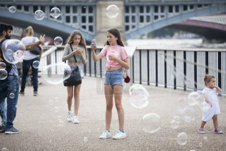 Girls take pictures of soap bubbles near South bank