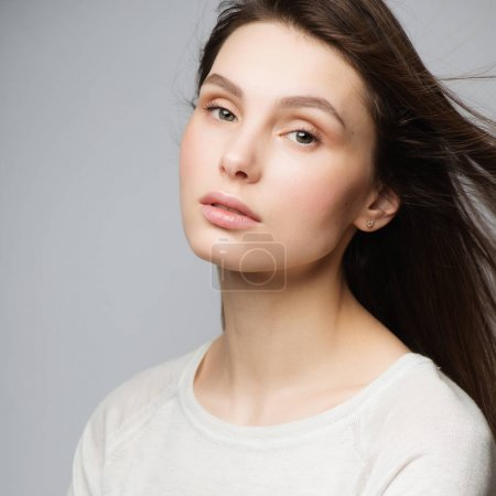Portrait of beautiful young woman with long brown ...