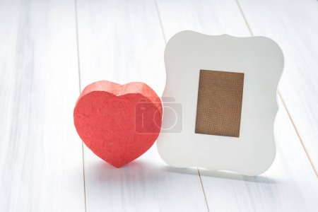 White vintage frame with red heart gift box on white wood table