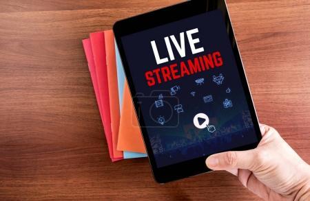 Photo pour Vue de dessus de la main tenant la tablette avec Live à la vapeur de mot avec icône sur portable couleur sur table en bois haut, Digital business concept. - image libre de droit