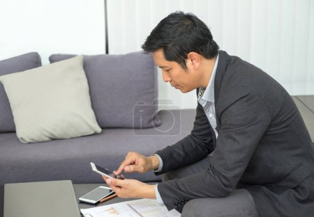 Businessman sitting at sofa and looking down at mobile phone scr