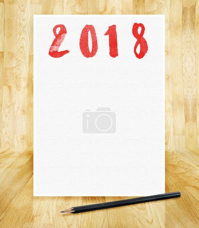 Happy new year 2018 on white paper frame with pencil in hand bru