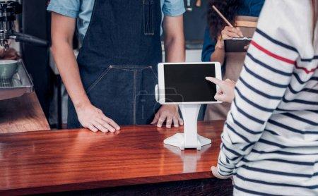 Photo pour Client self-service commander un menu de boissons avec écran de tablette au comptoir bar café, vendeur café accepter le paiement par mobile.digital concept de style de vie. - image libre de droit