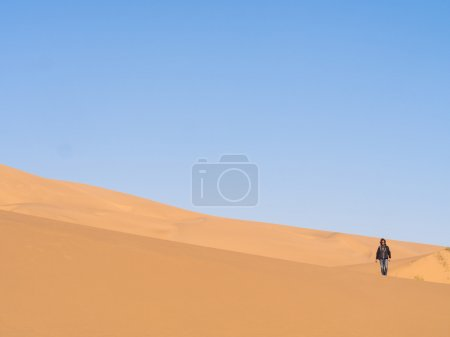 Single man walking on desert