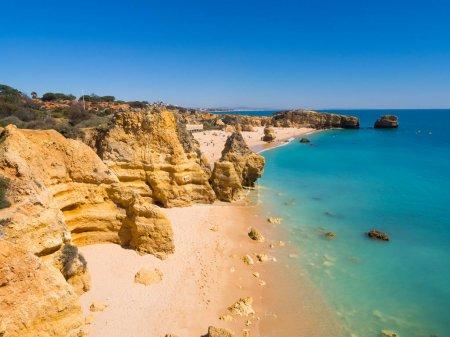 rocky Sao Rafael beach or Praia de Sao Rafael with clean blue water in Algarve region at hot summer time, Portugal.