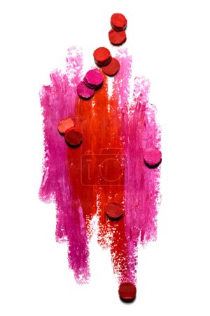 Lipstick strokes. Creative photo of an abstract red and pink strokes with slices of lipstick isolated on white.