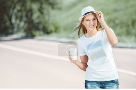 Photo for Beautiful young woman with a takeaway coffee cup, walking on the road, drinking coffee, and smiling against road background. - Royalty Free Image